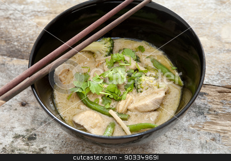 Thai green curry with chopsticks stock photo, Bowl of delicious healthy creamy Thai green curry with diced chicken pieces served with chopsticks, high angle view by Stephen Gibson