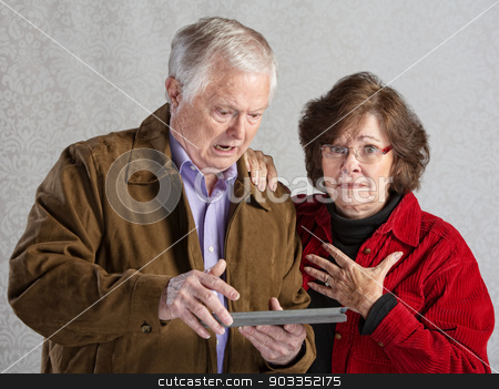 Upset with Technology stock photo, Angry man using tablet with embarrassed woman by Scott Griessel