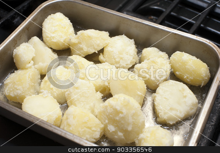 Preparing roast potatoes stock photo, Preparing roast potatoes by par boiling them and placing them in an oven dish with oil to roast and crisp up by Stephen Gibson