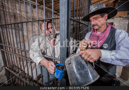Sheriff Tends to Prisoner stock photo, Sheriff Tends to a Prisoner In a Cell by Scott Griessel