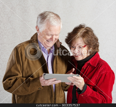 Excited Couple with Tablet stock photo, Senior male and female excited with computer tablet by Scott Griessel