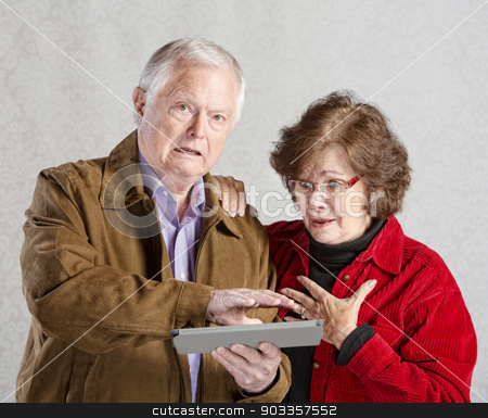 Embarrassed Man with Tablet stock photo, Embarrassed senior man covering his tablet computer by Scott Griessel