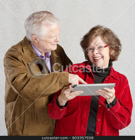 Man Looking at Woman's Tablet stock photo, Confused man pointing at smiling womans tablet by Scott Griessel