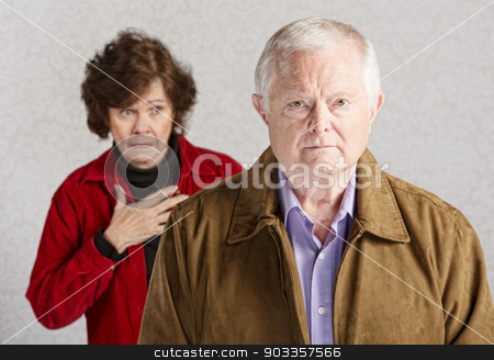 Worried Wife stock photo, Concerned senior woman with hand on chest behind sad man by Scott Griessel
