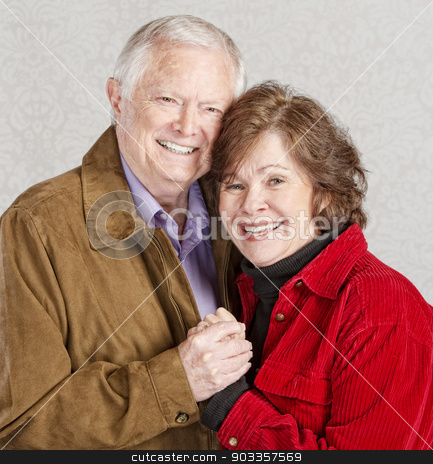 Embracing Senior Couple stock photo, Smiling Caucasian older couple embracing and holding hands by Scott Griessel