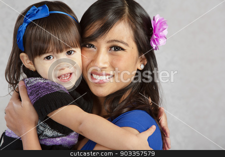Smiling Mother and Daughter stock photo, Happy young mother and female toddler hugging each other by Scott Griessel