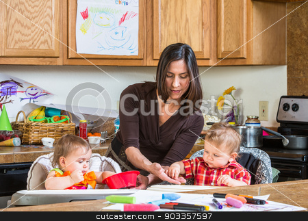 Mother Feeds Babies stock photo, A mother in the kitchen feeds babies breakfast by Scott Griessel