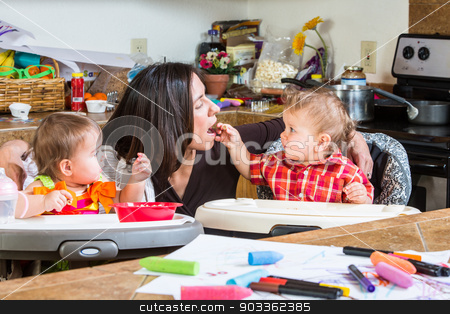 Baby Feeds Mother stock photo, Baby feeds his mother cereal at breakfast by Scott Griessel