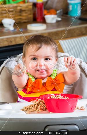 Baby Girl Eats Breakfast stock photo, Baby girl eats breakfast in her highchair by Scott Griessel