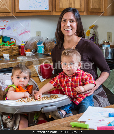 Mother Smiles With Babies stock photo, Mother poses with children in the kitchen by Scott Griessel