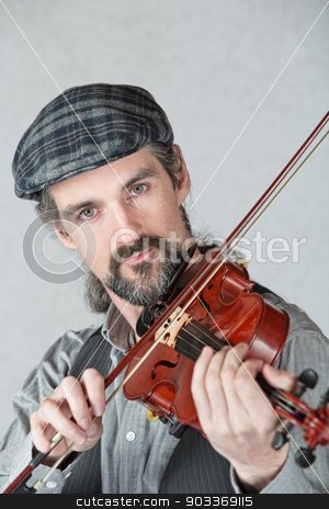 Irish Man Playing Fiddle stock photo, Serious Irish man playing a fiddle over gray background by Scott Griessel