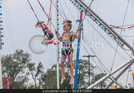 Girls jumping at state fair stock photo, DES MOINES, IA /USA - AUGUST 10: Unidentified girls jumping in harnesses on carnival jumping apparatus at the Iowa State Fair on August 10, 2014 in Des Moines, Iowa, USA. by Scott Griessel