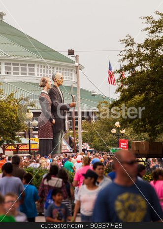 Crowd and American Gothic Sculpture at Iowa State Fair stock photo, DES MOINES, IA /USA - AUGUST 10: Attendees at the Iowa State Fair. Thousands of people filling the midway at the Iowa State Fair on August 10, 2014 in Des Moines, Iowa, USA. by Scott Griessel