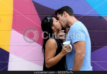 Kissing stock photo, A in love couple kissing in front of a wall. by Henrik Lehnerer