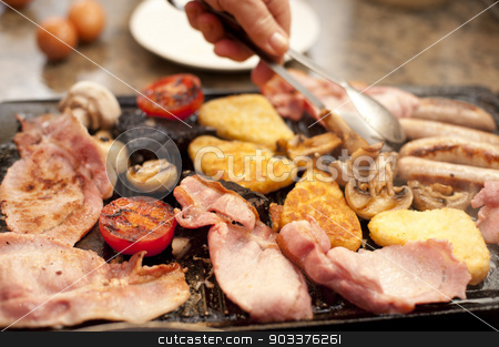 Man serving a hearty cooked breakfast stock photo, Man serving a hearty cooked breakfast warming on the griddle with bacon, tomato, hash browns, mushrooms and sausages by Stephen Gibson