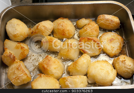 Delicious golden crispy roast potatoes stock photo, Delicious golden crispy roast potatoes in a baking tray fresh from the oven, high angle view by Stephen Gibson