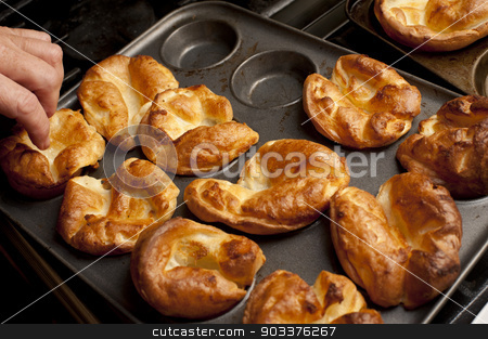 Man removing Yorkshire puddings from a baking tray stock photo, Man removing freshly baked individual fluffy golden Yorkshire puddings from a baking tray by Stephen Gibson