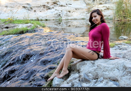 Hispanic Woman Creek stock photo, Hispanic woman sitting at water edge of a creek. by Henrik Lehnerer