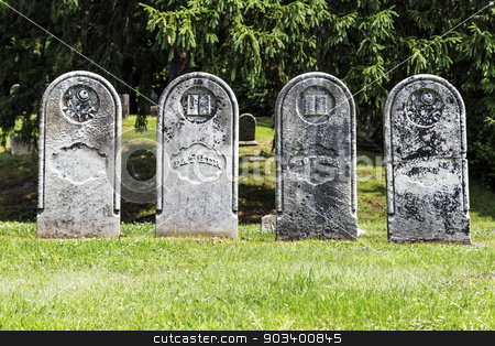 Four Antique Gravestones stock photo, Four weathered and historic headstones in a row. Classic gravestone shape.  by Leah Fallesen