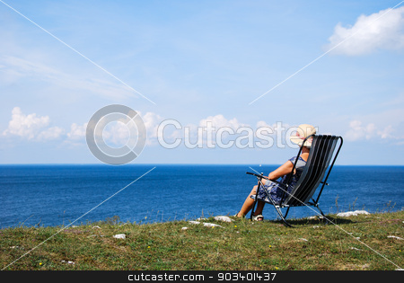 Relaxing at the coast stock photo, Woman sitting in a chair with beautiful view by the Baltic sea in Sweden by Birgitta Kullman