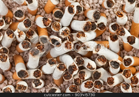 Cigarettes chaos closeup stock photo, Ashtray full of smoked cigarettes in the sand closeup from above  by Dario Rota