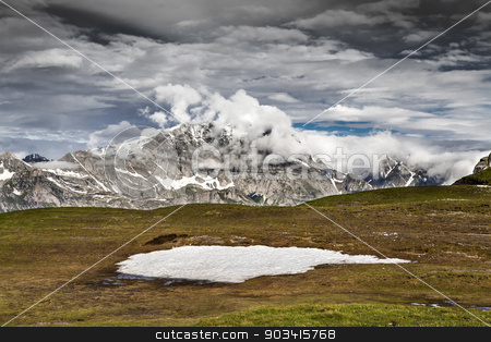 Mountain landscape with clouds stock photo, Alpine landscape with green grass, blue sky and heavy white clouds  by Dario Rota