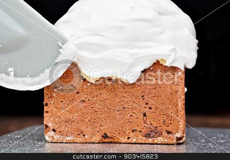 Spreading cream on cake with spatula stock photo, Spreading cream on christmas cake icing with spatula  by Dario Rota