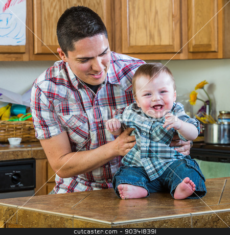 Father Plays With Baby stock photo, Father plays with laughing baby in kitchen by Scott Griessel
