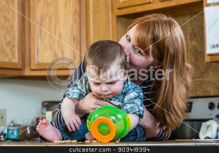 Mother Plays With Her Baby stock photo, Mother in kitchen plays with her baby by Scott Griessel