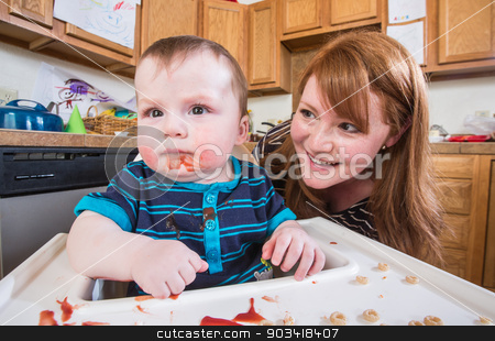 Woman Feeds Baby in Kitchen stock photo, A woman feeds her baby breakfast in the kitchen by Scott Griessel