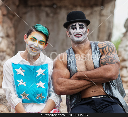 Strong Man with Cirque Clown stock photo, Laughing clown with stars and muscular man in hat by Scott Griessel