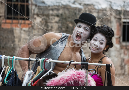 Laughing Attractive Clowns stock photo, Laughing cirque clowns with makeup at clothing rack by Scott Griessel