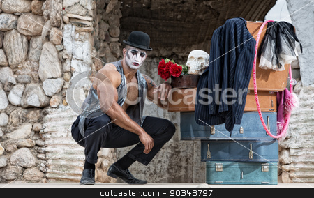 Handsome Cirque Performer Kneeling stock photo, Handsome muscular cirque performer kneeling next to luggage by Scott Griessel
