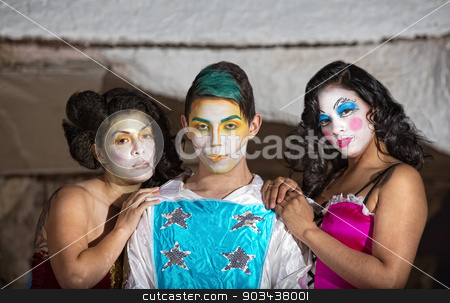 Grinning Cirque Clown with Admirers stock photo, Grinning cute cirque performer with female admirers by Scott Griessel