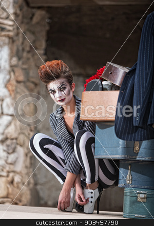 Clown Near Luggage stock photo, Cute female comedia del arte performer next to luggage by Scott Griessel
