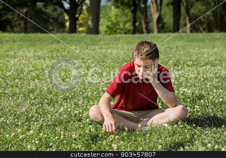 Sad Teen Looking Down stock photo, Sad young Caucasian male sitting on grass by Scott Griessel