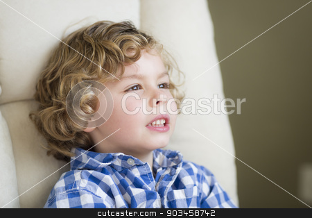 Cute Blonde Boy Daydreaming and Sitting in Chair stock photo, Cute Young Blonde Boy Daydreaming and Sitting in Chair. by Andy Dean