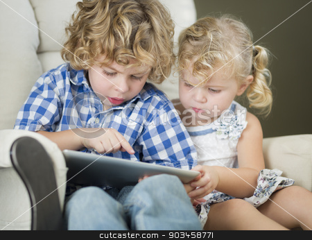 Young Brother and Sister Using Their Computer Tablet Together stock photo, Adorable Young Brother and Sister Using Their Computer Tablet Together. by Andy Dean