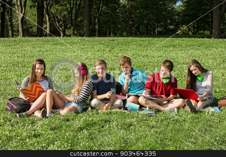 Teens Studying Together stock photo, Teens with headphones and textbooks studying outdoors by Scott Griessel