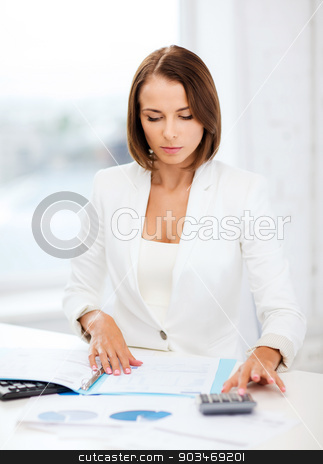 businesswoman working with calculator in office stock photo, business concept - businesswoman working with calculator in office by Syda Productions