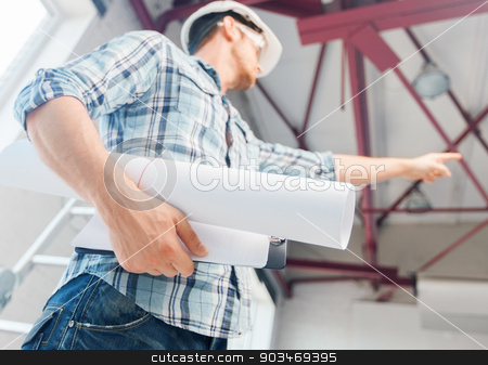 man with blueprint stock photo, architecture and home renovation concept - man in helmet and gloves with blueprint showing direction by Syda Productions
