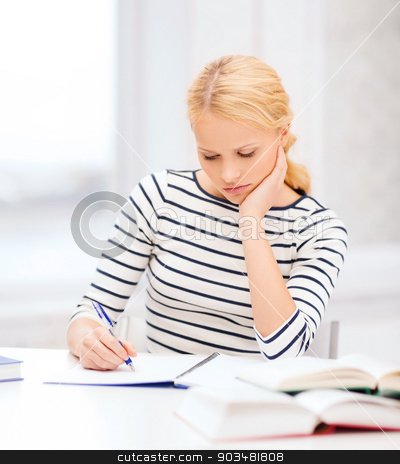concentrated woman studying in college stock photo, education, school and business concept - concentrated woman with books and notebook studying in college by Syda Productions