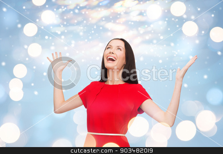 smiling young woman in red dress with hands up stock photo, happiness and people concept - smiling young woman in red dress with hands up by Syda Productions