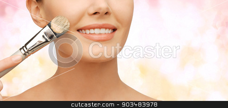 beautiful woman with brush stock photo, beauty amd make-up concept - closeup picture of beautiful woman with brush applying cream foundation by Syda Productions