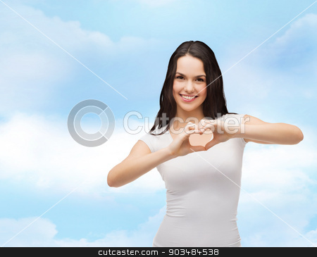smiling girl showing heart with hands stock photo, love, t-shirt design and happy people concept - smiling girl in white blank t-shirts showing heart with hands by Syda Productions