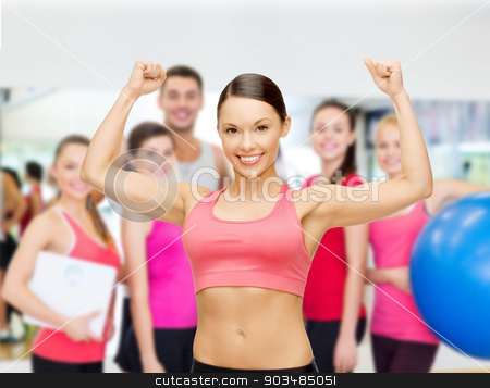 personal trainer with group in gym stock photo, fitness, sport, training and lifestyle concept - personal trainer with group of smiling people in gym by Syda Productions
