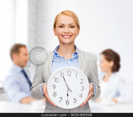 smiling businesswoman with wall clock stock photo, business and time concept - attractive businesswoman with wall clock by Syda Productions