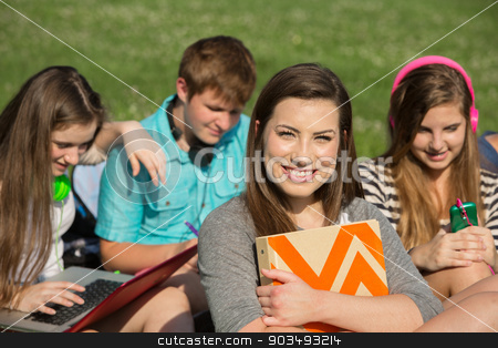 Cute Teen Holding Notebook stock photo, Cute teen girl holding binder with friends by Scott Griessel