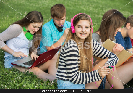 Teen Listening to Music stock photo, Happy teen with male and female friends outdoors by Scott Griessel