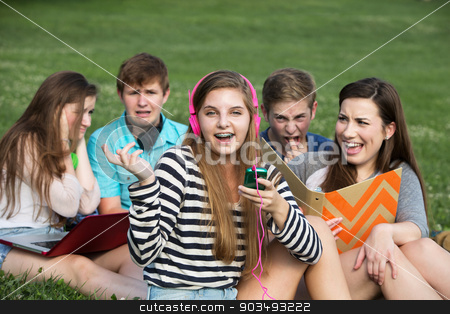 Singing Girl Annoying Friends stock photo, Singing teenage girl annoying friends studying outdoors by Scott Griessel